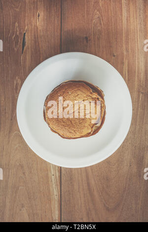 Homemade egg cupcake on white plate, on wooden table - Stock Image