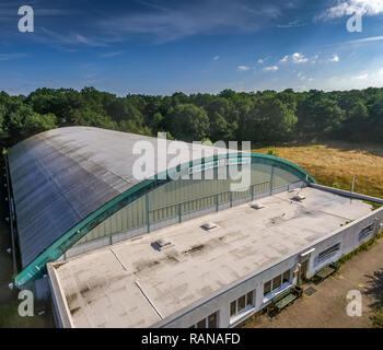 Wolfsburg, Germany, August 13., 2016: Aerial view of an old soccer hall which is no longer in operation with an arched roof and forest areas in the ba - Stock Image
