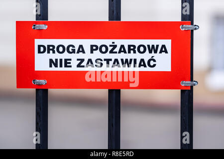 fire road, keep clear text in Polish on the sign mounted to the metal fence, white and red plate, black letters - Stock Image