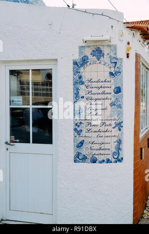 Trafaria, Portugal - Dec 16, 2018: Azulejo ceramic sign with typically Portuguese dishes for sale at a restaurant - Stock Image