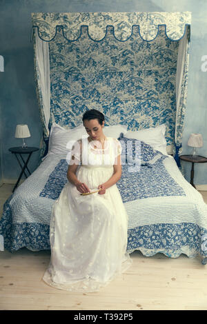Attractive young woman in authentic regency dress sitting on an antique bed - Stock Image