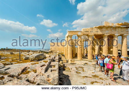 Crowds of tourists gather on their way to the Parthenon on Acropolis Hill in Athens, Greece with the city and Aegean sea in the background. - Stock Image