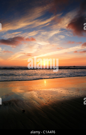 A vibrant sunset fades behind the ocean's horizon. It reflects vibrant colors in the sky, clouds and on the - Stock Image