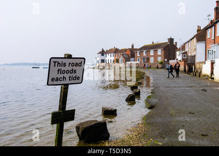 Road floods warning sign on seafront as tides goes out from Bosham creek in Chichester harbour. Shore Road, Bosham, West Sussex, England, UK - Stock Image