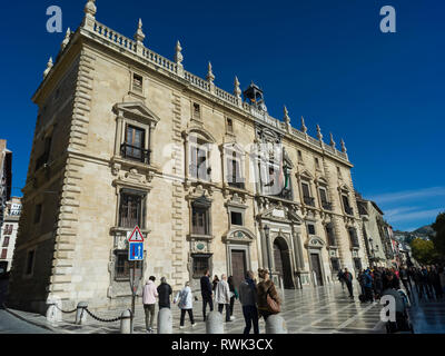 Pedestrians walking past a building in Plaza Neuva with bright blue sky; Granada, Andalusia, Spain - Stock Image