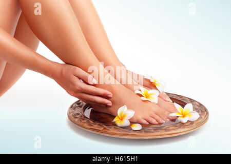 Beautiful womens legs and frangipani flowers over isolated background, beauty treatment, perfect skin waxing, pedicure - Stock Image