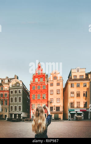 Woman tourist sightseeing Stockholm city Gamla Stan traveling lifestyle girl taking photo by smartphone Europe trip vacations - Stock Image