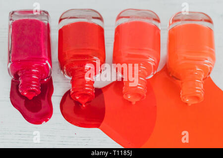 nail polish bottles in different shades of red to orange and purple spilling color on wooden surface, concept of cosmetics industry and manicure - Stock Image