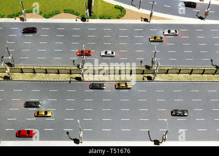 Model of a multi lane highway or motorway with cars travelling in both directions and central median - Stock Image