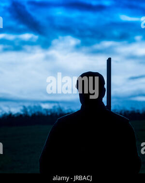 A man stood with his shotgun in the twilight at the end of a days shooting - Stock Image