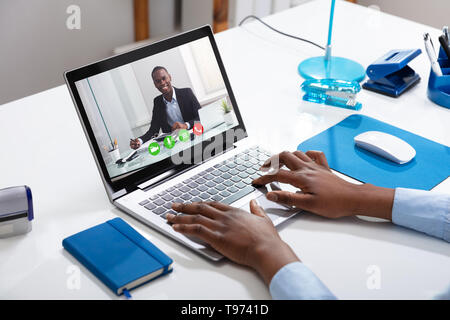 Close-up Of A Businessperson's Videoconferencing With Male Colleague On Laptop - Stock Image