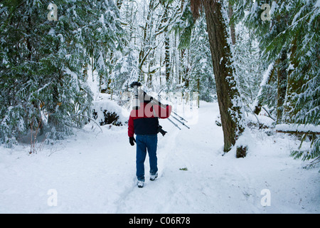 Male photographer carrying his gear through snowy forest-Goldstream Provincial park, Victoria, British Columbia, - Stock Image