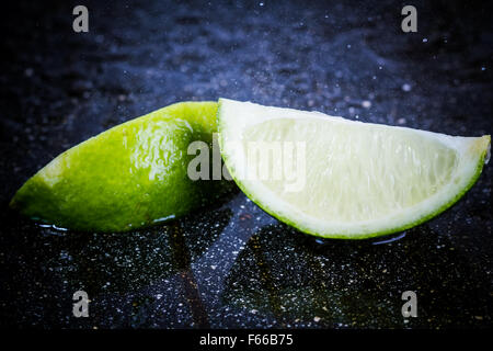 lime on a black marble desk closely - Stock Image