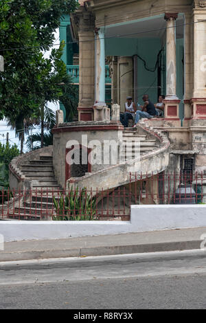 Three Cuban men chatting on the terrace of an old dilapidated Cuban house with amazing curved staircase. Havana Cuba - Stock Image