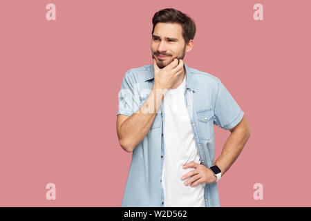 Portrait of confused handsome bearded young man in blue casual style shirt standing scratching beard and thinking what to do or try to find answer. in - Stock Image