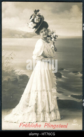 A postcard printed in Germany, shows a beautiful woman in white dress and hat with flowers. The inscription in German: - Stock Image