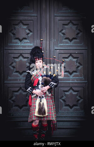 A Scottish piper playing the bagpipes in front of a large ornate door - Stock Image