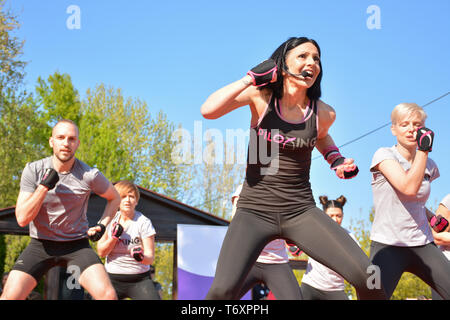 Nis, Serbia - April 20, 2019 Instructor and peoples group outdoor Piloxing gathering in park training on sunny day - Stock Image