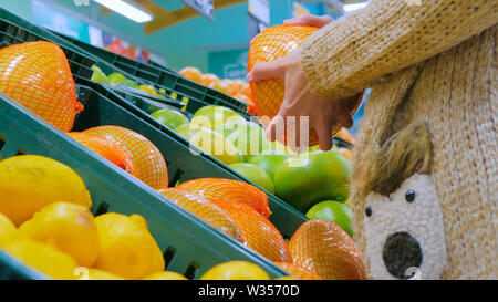 Woman buying fresh exotic citrus fruits at grocery store - Stock Image