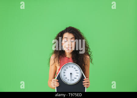 Photo of fitness woman 20s wearing summer clothes holding weigh scale during exercises against green wall - Stock Image