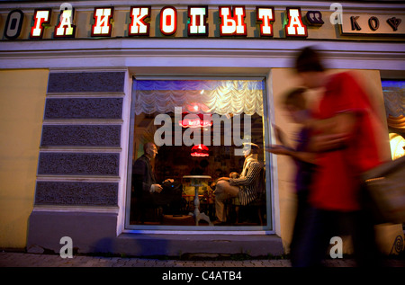 Russia, Golden Ring, Kostroma; Youths walking along the streets in town in front of a stylish restaurant - Stock Image