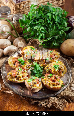 Baked potatoes in jacket stuffed with bacon, mushrooms and cheese served on rustic plate. Top view - Stock Image