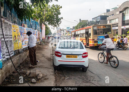 A man urinates by the side of the road in Chennai, India - Stock Image
