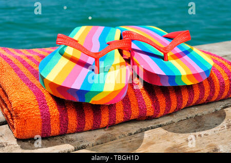 closeup of a pair of rainbow-patterned flip-flops on a orange beach towel, on a weathered dock, next to the ocean or a pond - Stock Image