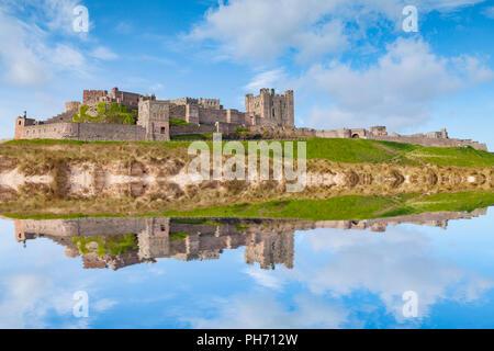 Bamburgh Castle, Northumberland, at high tide - Photoshop effect. - Stock Image