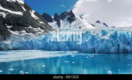 Blue and turquoise color glacier with reflections on calm water in Drygalski Fjord, South Georgia Island, viewed from Antarctic cruise ship. - Stock Image