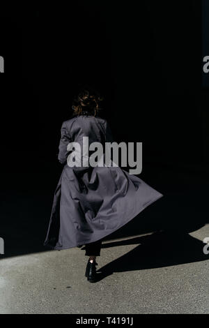 Rear view of a Woman walking away wearing a trench coat - Stock Image