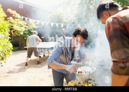 Male friends barbecuing in sunny backyard - Stock Image