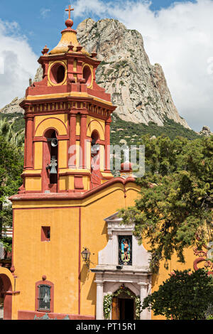 The Parroquia San Sebastian church with the massive monolith rock called the Pena de Bernal in the beautiful colonial village of Bernal, Queretaro, Mexico. Bernal is a quaint colonial town known for the Pena de Bernal, a giant monolith which dominates the tiny village is the third highest on the planet. - Stock Image