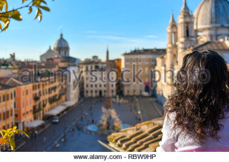A young woman gazes out over the Piazza Navona from a rooftop terrace on a summer morning in the historic center of Rome, Italy - Stock Image