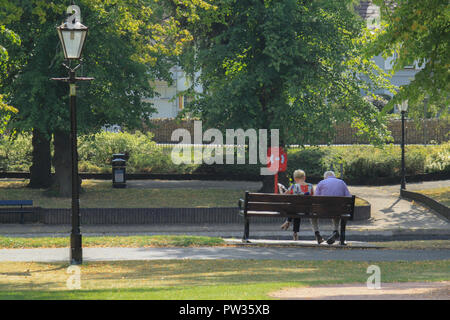 A man and a woman sat on a bench by the river in Abbey Park Evesham - Stock Image