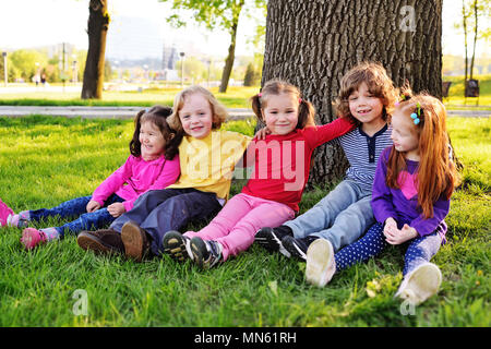 a group of small children in colorful clothes embracing sitting on the grass under a tree in a park laughing and smiling. - Stock Image