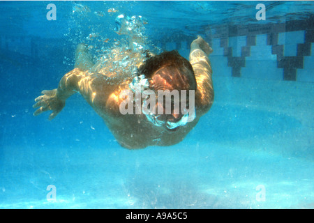 Man swimming underwater in swimming pool - Stock Image