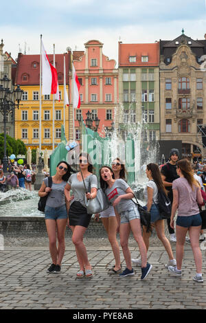 Selfie teenage girls, a group of teenagers pose for a selfie photo in the Market Square in the central Old Town area of Wroclaw, Poland. - Stock Image