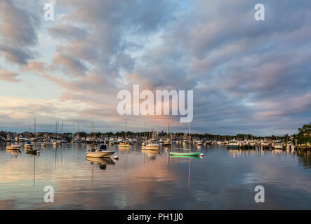The rising sun adds color to dramatic clouds over sunlit boats in the harbor shortly after sunrise in Oak Bluffs, Massachusetts on Martha's Vineyard. - Stock Image