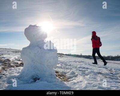 Real icy snowman standing in winter landscape. Hot spring sun and some people walk at horizon - Stock Image