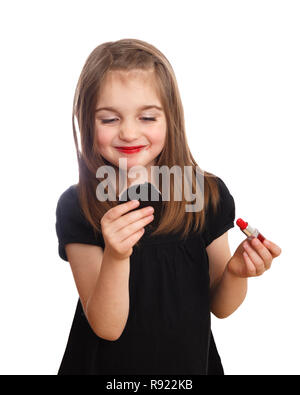 Cute young girl looking into compact mirror putting on red lipstick - Stock Image