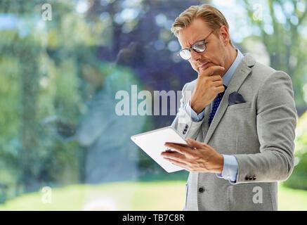 Businessman holding iPad - Stock Image