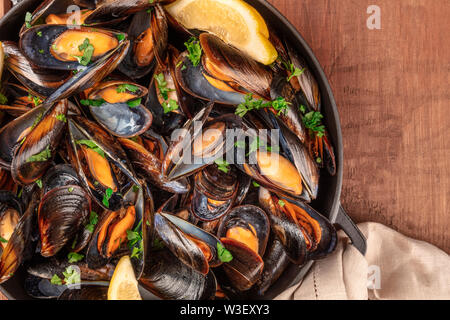 Marinara mussels, moules mariniere, with lemon slices, in a cooking pot, overhead close-up view, shot from the top on a dark rustic wooden background - Stock Image