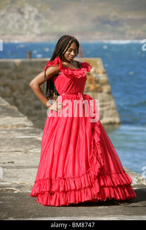African Woman with Dreadlocks, Wearing a Red Dress, Standing on Quay by the Sea. - Stock Image