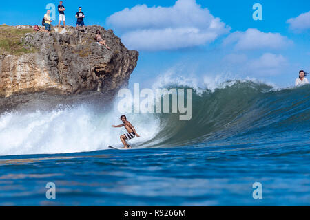 View of young male surfer riding wave in sea, Jimbaran, Bali, Indonesia - Stock Image