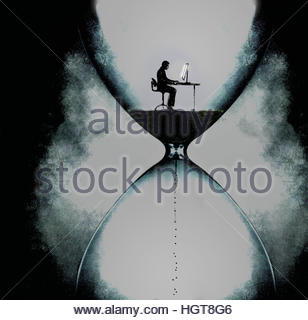 Businessman working on computer inside dark hourglass with time running out - Stock Image