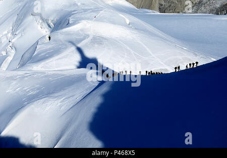 Climbers descending the Aiguille de Midi win the French Alps, with the shadow of the tower cast across the mountain - Stock Image