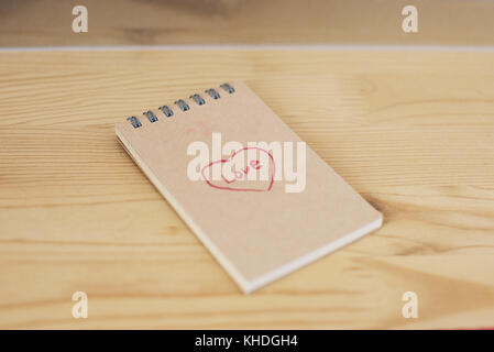 Note pad with heart shape and word love written on cover - Stock Image