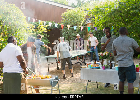 Male friends playing ping pong, enjoying backyard barbecue - Stock Image
