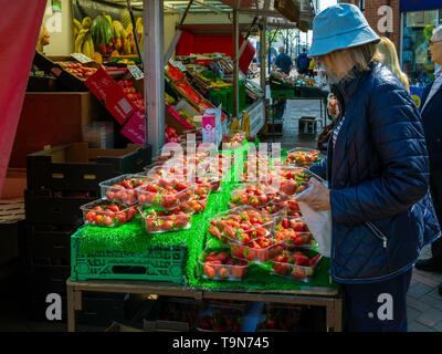 A senior lady customer carefully choosing bargain price strawberries  at a greengrocer and fruiterers market stall in Redcar Town Centre - Stock Image